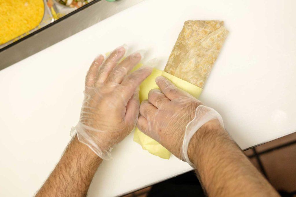 Robertito's employee wrapping a burrito